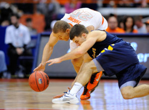 Billy Baron and Syracuse Orange guard Brandon Triche (20) battle for a loose ball during the second half at the Carrier Dome. Syracuse defeated Canisius 85-61. (Photo by Rich Barnes-USA TODAY Sports)