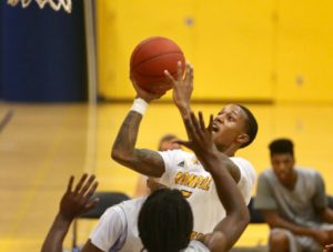 Omar Williams (center) gets in the lane for two of his game-high 20 points. (Photo courtesy of Monroe CC Athletics)